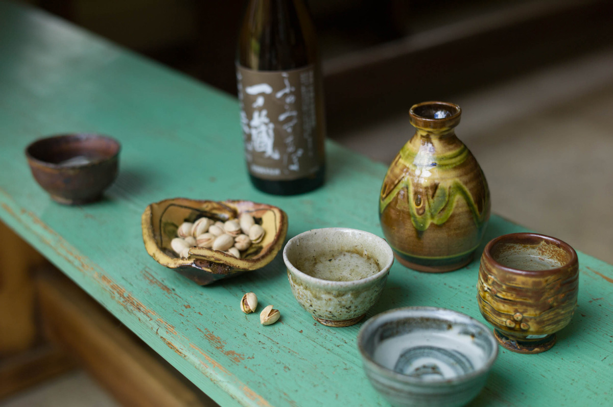 Sake with bottle by Clive Bowen, guinomi by Phil Rogers, Nic Collins & Mike Dodd, and pistachios in a dish by Jean-Nicolas Gérard