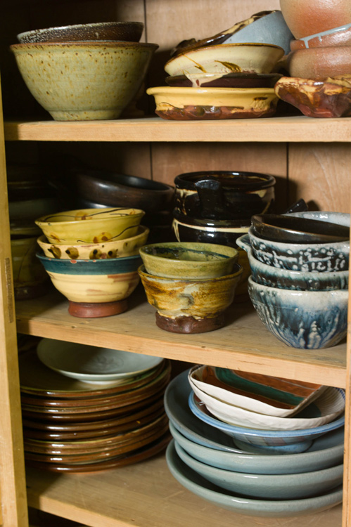 Stacks of homemade pots in a kitchen cupboard